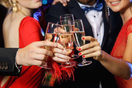 Group of people during celebration. Hands with a full glasses of sparkling wine. Stock Photo