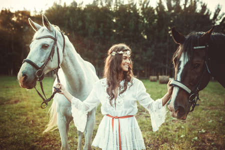 Young woman in beautiful white dress and her beautiful horses