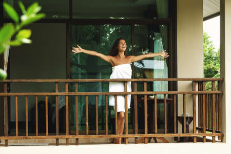 Vacations in tropical warm country. Happy and beautiful woman on the balcony after shower. Фото со стока - 133671456