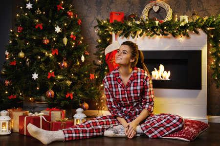 Glückliche Frau mit karierten Pyjamas sitzt neben dem Kamin mit Weihnachtsschmuck