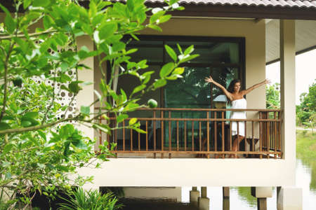 Vacations in tropical warm country. Happy and beautiful woman on the balcony after shower. Фото со стока - 133671466