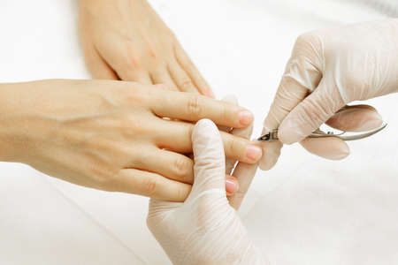 Manicure master during work. Close up of hands with a nipper
