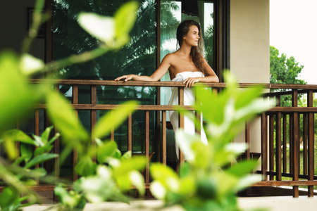 Vacations in tropical warm country. Beautiful woman on the balcony after shower.