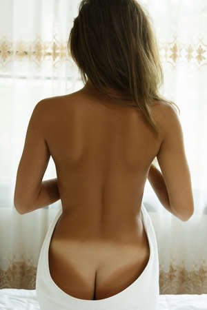 Female back and buttocks with white trace after sunbathing