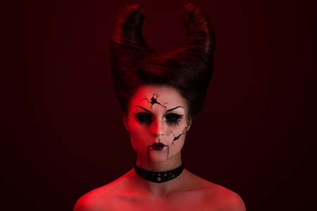 Model in creative image. Spooky porcelain doll with horns on her head. Stok Fotoğraf