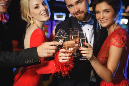 Grupo de gente feliz durante la celebración está bebiendo vino espumoso en el casino