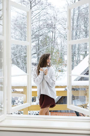 Happy woman with a cup of hot drink is standing on the balcony at snowy winter day Stock Photo