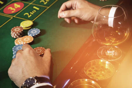 Man playing roulette in the casino. Close up of male hands with a glass of cognac and chips.