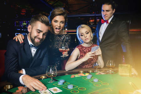 Losers and winners. Group of rich people is playing poker in the casino.