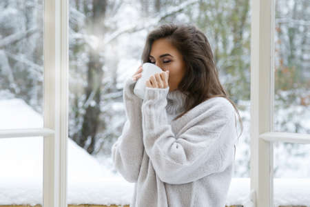 Woman with cup of hot drink at snowy winter day