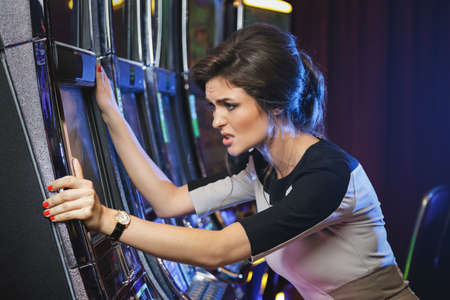 Addicted gambler. Angry woman is lose everything, during slot machines game in the casino
