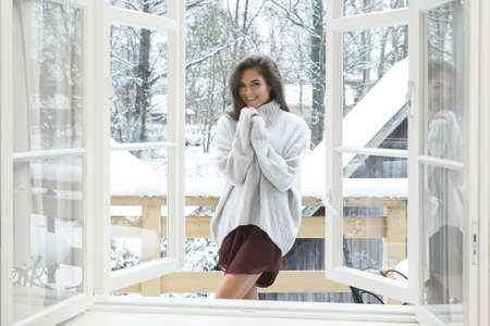 Happy woman is standing on the balcony at snowy winter day
