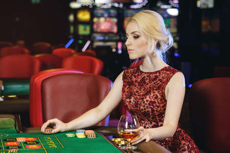 Young blonde woman wearing beautiful red dress is playing roulette in the casino Foto de archivo