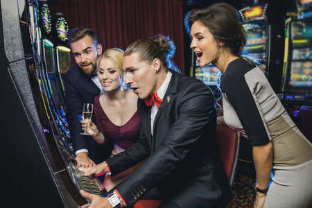 Group of friends playing slot machines in the casino Foto de archivo