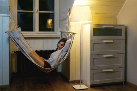 Woman wearing woolen pullover is lying in the hammock
