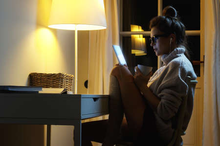 Young woman wearing a warm pullover is using tablet PC in the middle of the night
