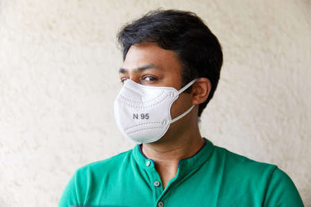 Mid Shot of Adult South Asian Indian Male wearing N95 white respirator and green polo t-shirt with Face looking left of camera