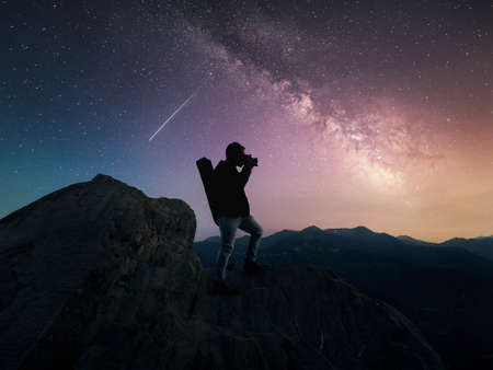 Silhouette of man on cliff standing under milky way galaxy 写真素材
