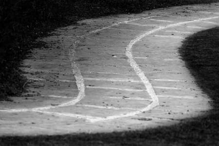 Black and white shot of an S curved pathway