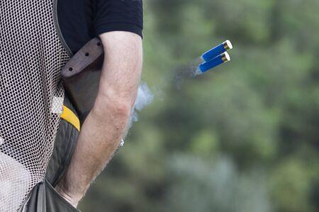 hombre disparando: Escopeta lanzando su concha