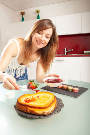 Young blonde caucasian woman smiling and pouring strawberry jam to a heart shaped cheesecake in a kitchen.
