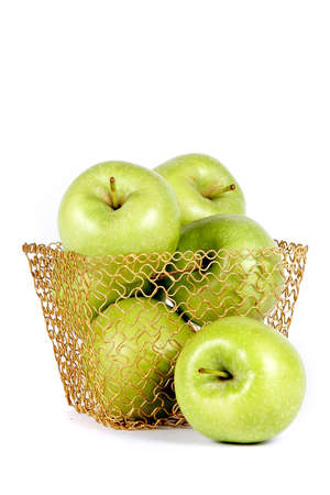 Green celebratory apples lie in a gold basket on a white background
