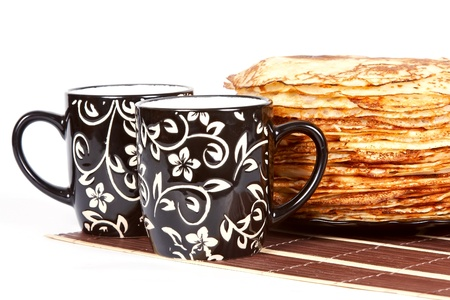 Cups with tea and a pile of pancakes on a plate photo