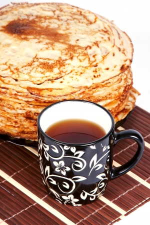 Cup with tea and a pile of pancakes on a plate Stock Photo