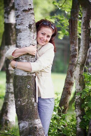 The beautiful woman embracing a birch