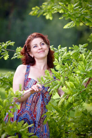 The beautiful woman with oak branches Stock Photo