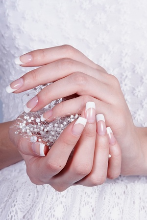 Beautiful female hands with manicure against a white dress