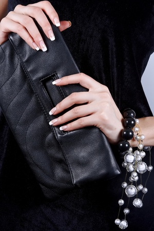 Beautiful female hands with manicure hold a black handbag