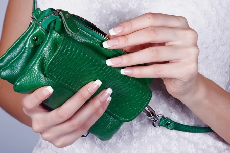 Beautiful female hands with manicure hold an open green handbag