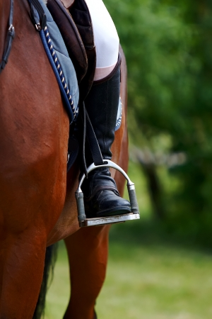 Foot of the athlete in a stirrup astride a horse Standard-Bild - 15113939