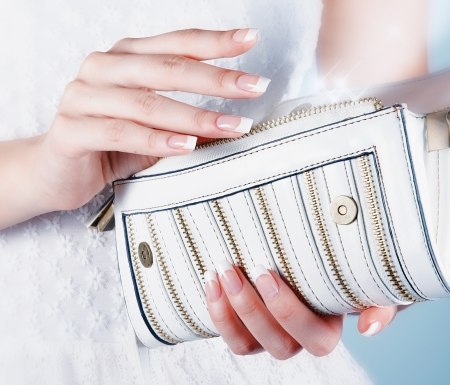 Beautiful female hands with manicure hold an open white handbag photo