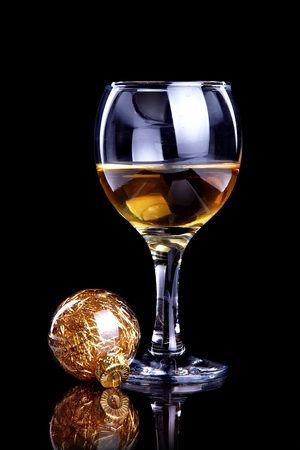 Glass with drink and a Christmas ball on a black background. Glass with alcohol and a Christmas ball. photo