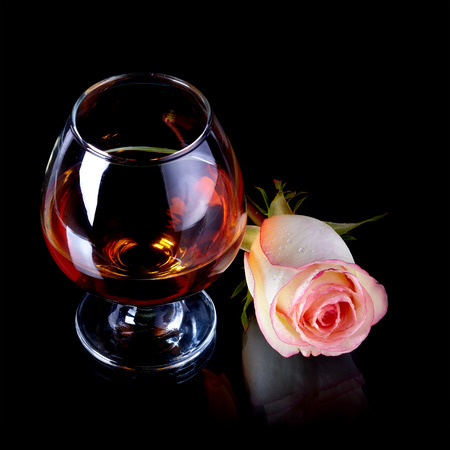 Glass and rose  Alcohol and flower  Glass with drink and a pink rose  photo