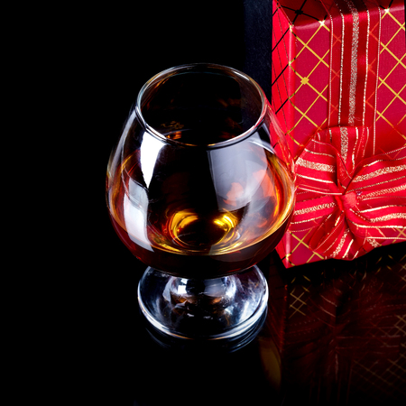 Glass with alcohol and a gift. Alcohol and gift box. Box with a bow and glass with drink. photo