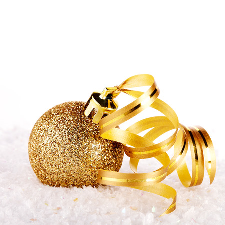 New Years golden ball on snow with a tape. New Years golden balls. Christmas balls. Christmas tree decorations. Christmas jewelry. Фото со стока