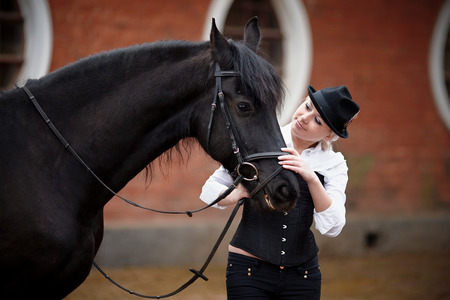 communicates: Portrait of the girl and black horse. The girl communicates with a beautiful horse. Equestrian sport.