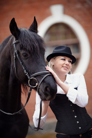 Portrait of the girl and black horse. The girl communicates with a beautiful horse. Equestrian sport.