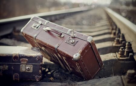 Two vintage brown suitcases are left to lie on railway rails. photo