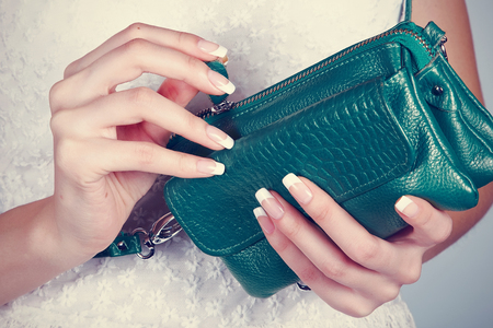 Beautiful female hands with manicure hold an open handbag photo