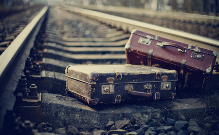 maleta: Dos pasadas de moda olvidadas unas maletas se encuentran en las vías del ferrocarril