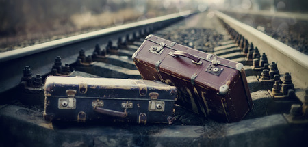 Two old vintage suitcases lie on railway tracks. photo