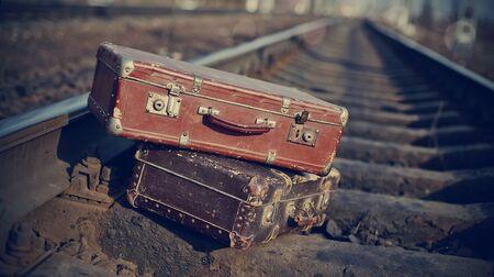 maleta: La imagen de dos maletas antiguas de la vendimia arrojado en los carriles ferroviarios.