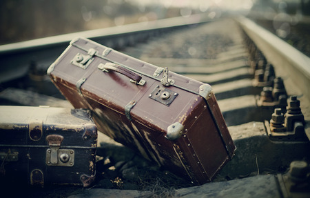 rail travel: Two old fashioned a suitcases on railroad tracks