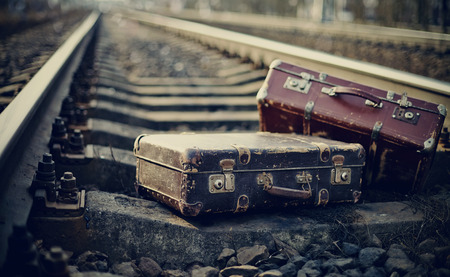 baggage: Old fashioned forgotten a suitcases lie on railway rails.