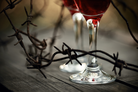 dependence: Rusty barbed wire and glasses with red wine on a table.  Alcoholic dependence. Stock Photo