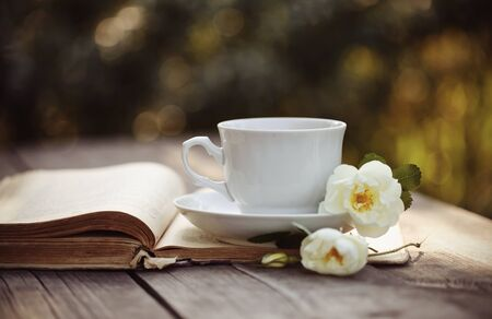 bible flower: White cup with a flowers of wild rose on an open old book on a wooden table.